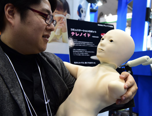 """An employee from Japan's robot venture Telenoid Planning chats with humanoid robot """"Telenoid"""", shaped like a child and composed of minimal human features such as a head, a face and upper body, developed by Osaka University professor Hiroshi Ishiguro at the annual International Robot Exhibition in Tokyo on December 3, 2015. The tele-operated android Telenoid enables it to be remote-controlled by sending voice and movement commands, captured with a camera. The robot, designed for remote education and elderly health care, will go on sale next year. Some 450 companies and organisations are displaying their latest robots with 5,000 people expected to visit during the four-day event.  AFP PHOTO / Yoshikazu TSUNO / AFP / YOSHIKAZU TSUNO        (Photo credit should read YOSHIKAZU TSUNO/AFP/Getty Images)"""