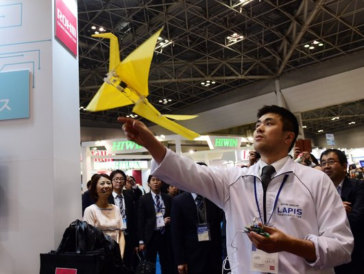 """An employee of Japan's electronics parts maker Rohm demonstrates a remote controlled flying paper crane """"Origami"""", weighing only 31g at the annual International Robot Exhibition in Tokyo on December 3, 2015. Some 450 companies and organisations are displaying their latest robots with 5,000 people expected to visit during the four-day event.  AFP PHOTO / Yoshikazu TSUNO / AFP / YOSHIKAZU TSUNO        (Photo credit should read YOSHIKAZU TSUNO/AFP/Getty Images)"""